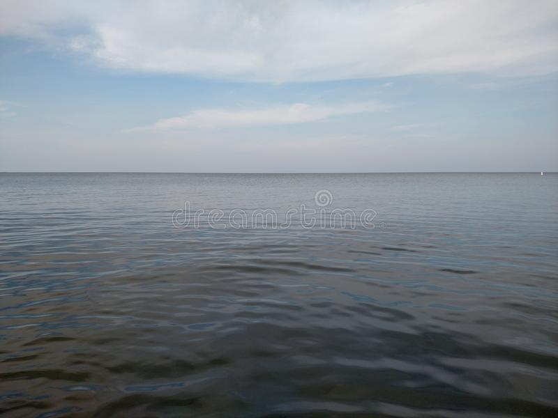 Calm water, ocean view and blue sky stock photo