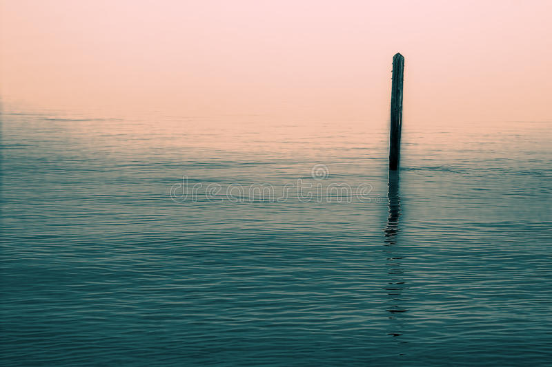Calm water with solitary wooden post and reflection. Serene image. stock images