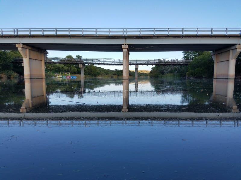 Calm water under a bridge stock images