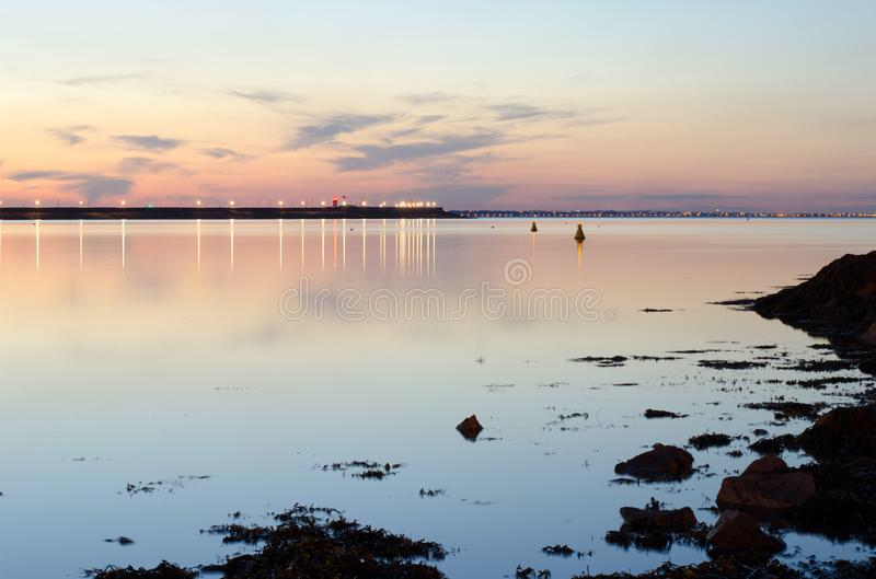 Calm waters of dublin bay,Ireland,at dusk. Flat calm waters of Irish sea,pier in the backround.Light of evening sky reflected off water surface stock photos