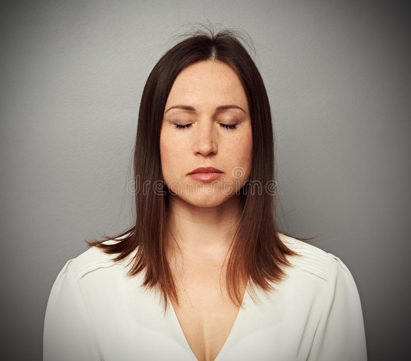 Calm woman with closed eyes. Over grey background stock photo