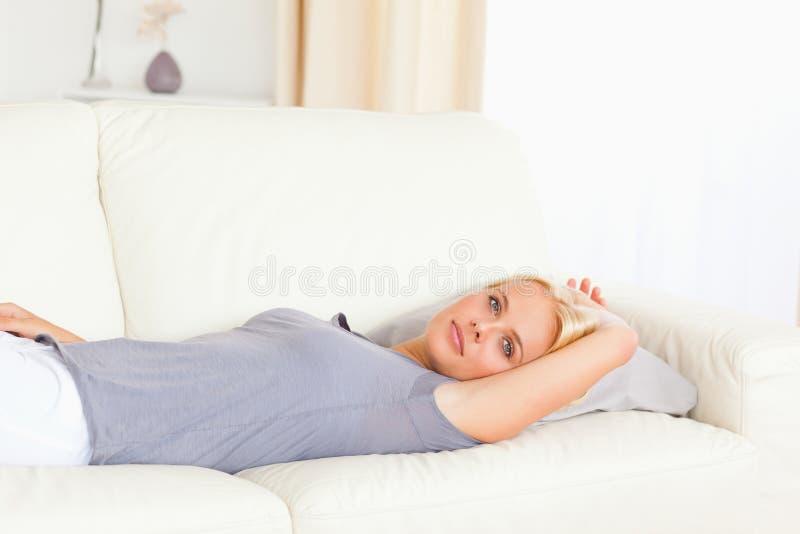 Calm woman lying on a sofa royalty free stock photos