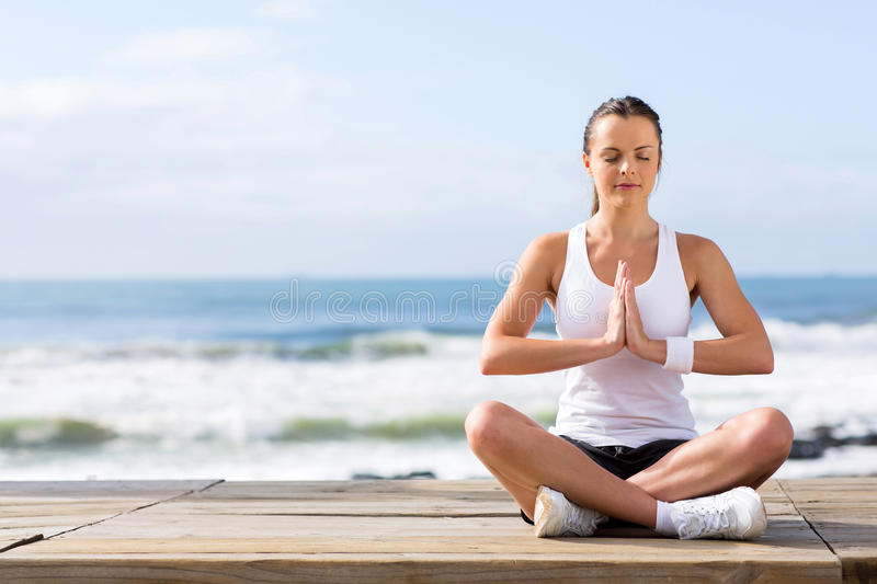 Calm woman meditating. Portrait of calm young woman meditating at the beach royalty free stock photo