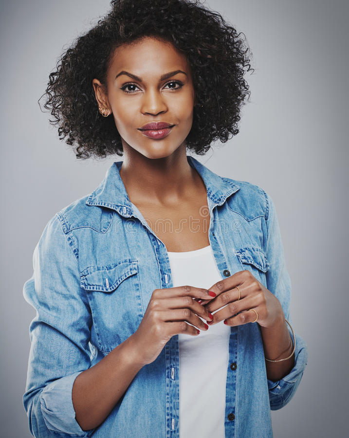 Calm woman wearing red nail polish on gray. Calm woman wearing red nail polish and blue jean shirt against gray background stock image