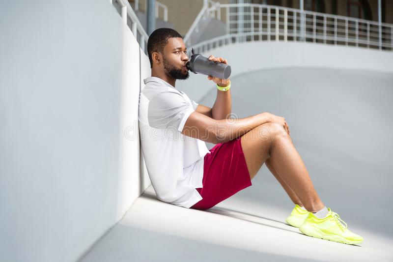 Calm young male athlete sitting at the stadium. Rest and recuperation. Calm attractive African American young male athlete sitting at the stadium and drinking stock photography