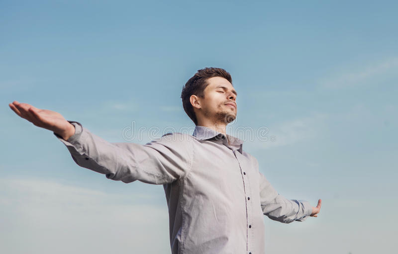 Calm young man portrait over blue sky royalty free stock image