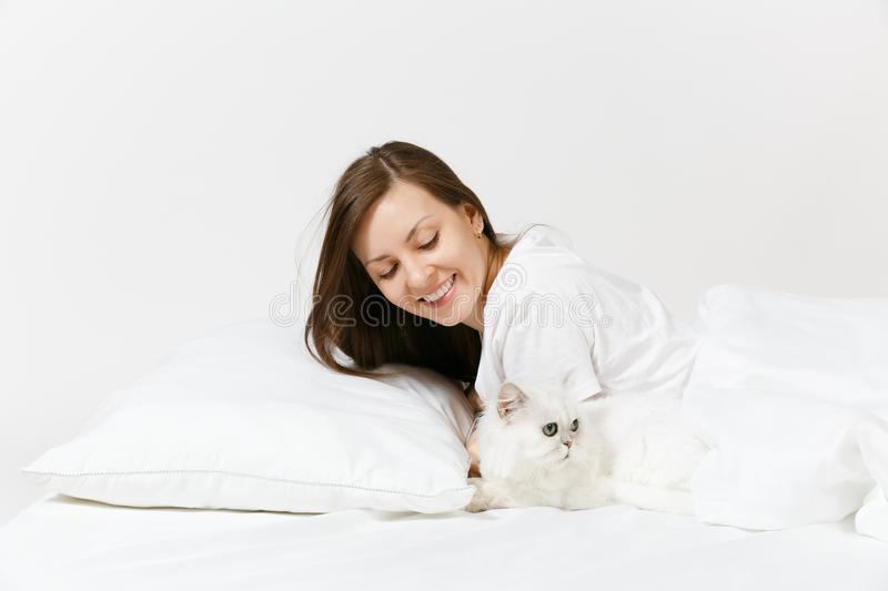 Calm young woman lying in bed with white cute Persian silver chinchilla cat, sheet, pillow, blanket on white background royalty free stock image
