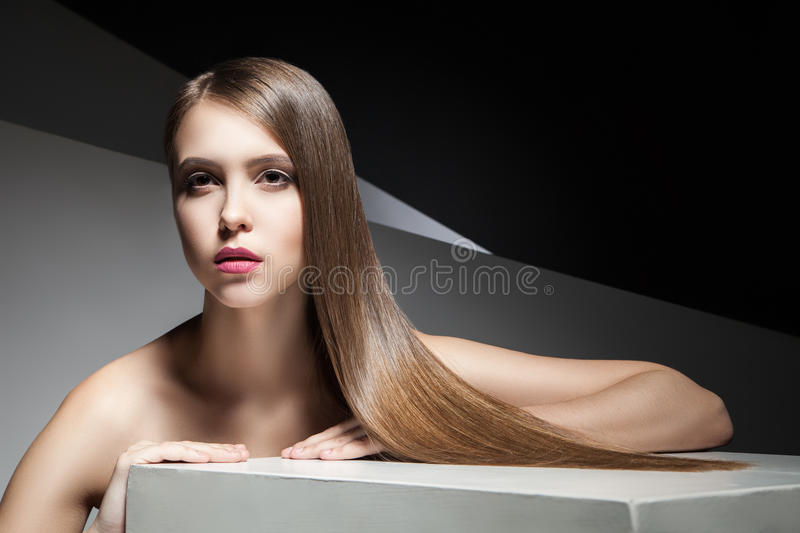 Calm young woman with shiny hair looking away stock images