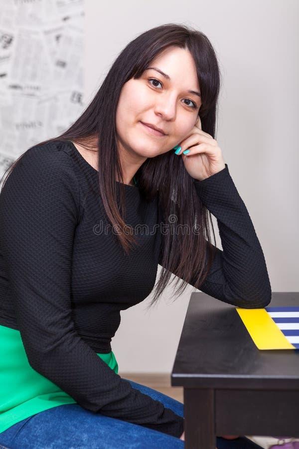 Calm young woman sitting at table, long dark hair stock image