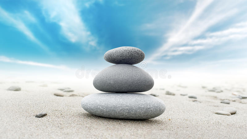 Calm zen meditate background with rock pyramid. At sandy beach with blue sky royalty free stock image