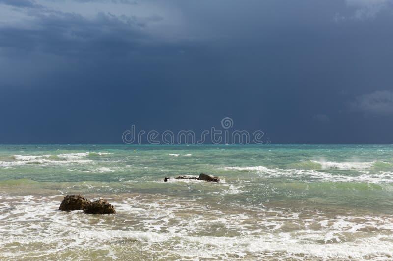 Calma antes de la tormenta, nubes oscuras con el mar iluminado por el sol imágenes de archivo libres de regalías