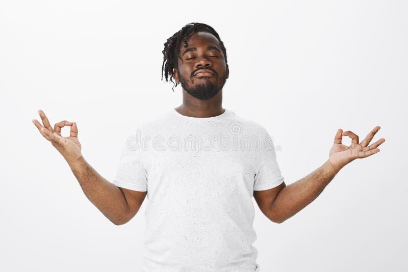 Calma de sensación y aliviado después de la meditación Retrato del novio afroamericano feliz confiado en equipo casual imagenes de archivo