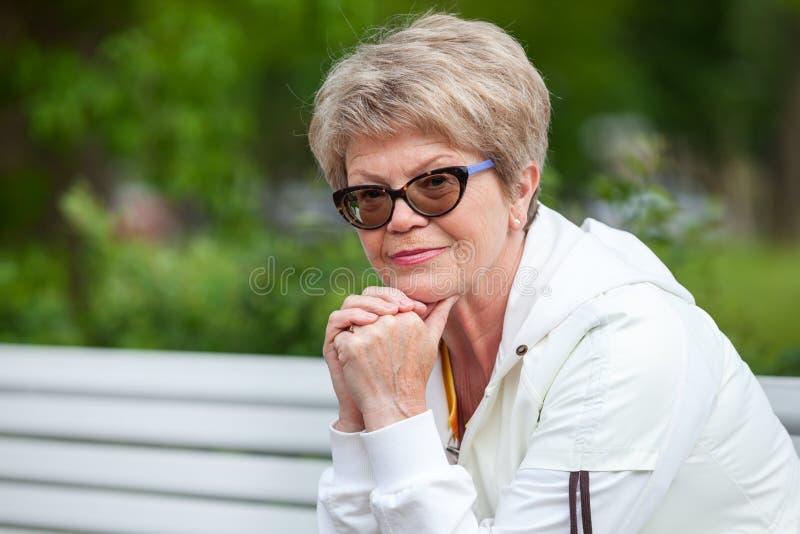 Calma e donna senior europea sorridente che esaminano macchina fotografica all'aperto Copi lo spazio immagine stock