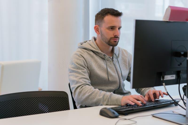 Calma joven y hombre concentrado que mecanografían en el teclado de ordenador que mira la pantalla imagen de archivo