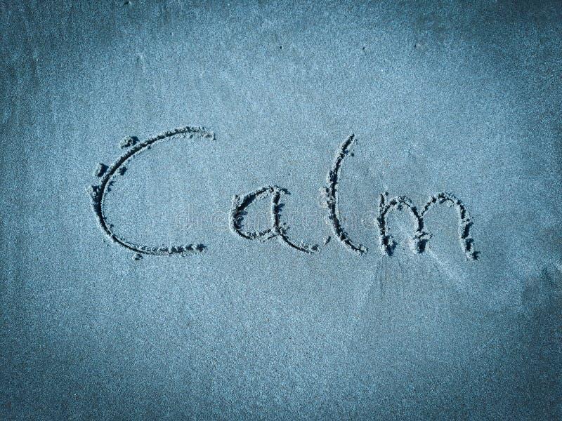 Calma, palavra escrita na areia azul imagens de stock