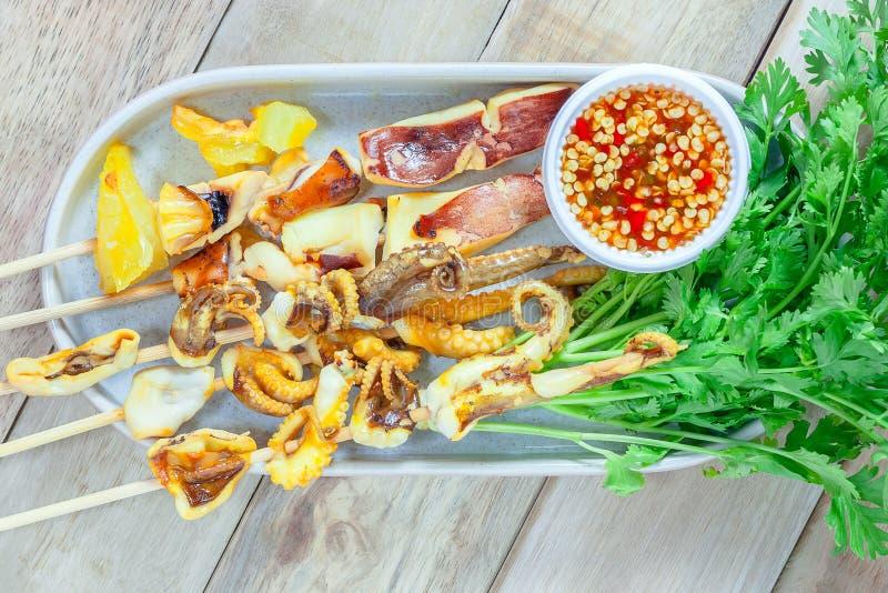 Calmar et légume grillés avec de la sauce à fruits de mer dans le plat blanc image libre de droits