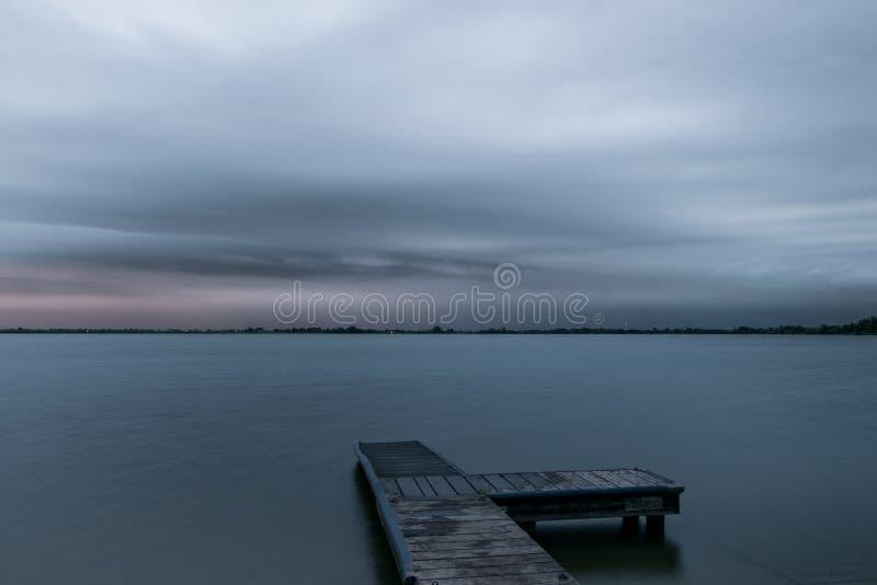 Calme avant la temp?te Un orage grave s'approche au-dessus de l'eau d'un lac aux Pays-Bas pendant l'heure bleue image stock