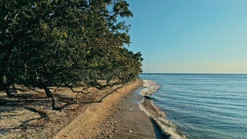 Calme et image aérienne de détente de bourdon d'un beau bord de mer à distance caché renversant d'océan au coucher du soleil avec photos stock
