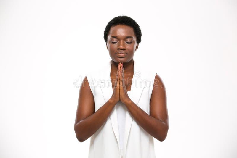 Calmi la donna abbastanza africana con gli occhi chiusi che stanno e che meditano fotografia stock
