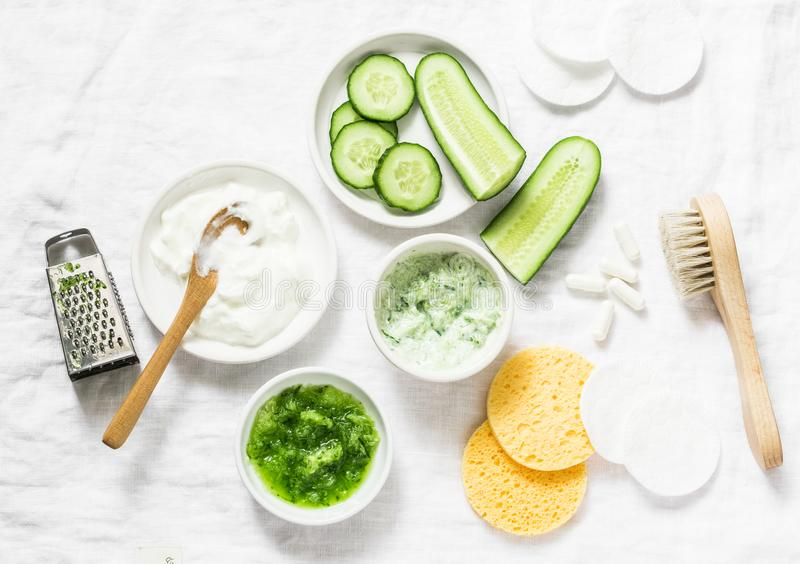 Calming cucumber yogurt mask. Ingredients for homemade cucumber face mask-cucumber, natural yogurt, probiotic capsule, sponges, br. Ush on white background, top royalty free stock image