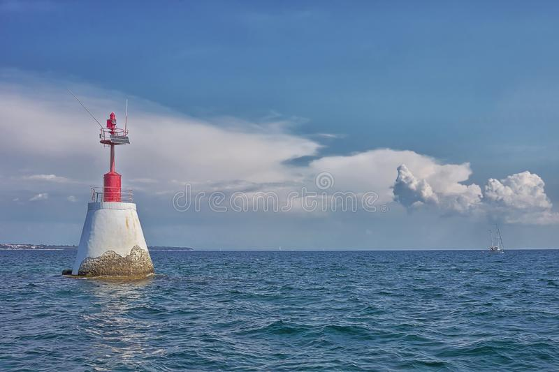 Lovely sea with small red lighthouse and a sailboat stock images