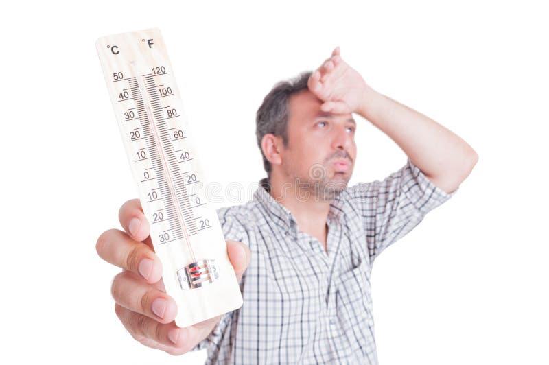 Calor de Sumer y concepto de la ola de calor con el hombre que sostiene el termómetro imagenes de archivo