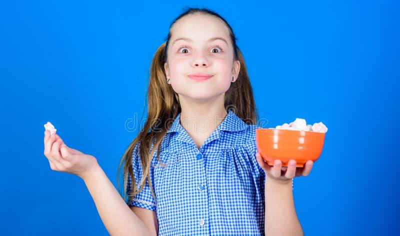 Calor?a y dieta Fondo azul dulce sonriente de las melcochas del cuenco del control de la cara de la muchacha a disposici?n Muchac fotografía de archivo