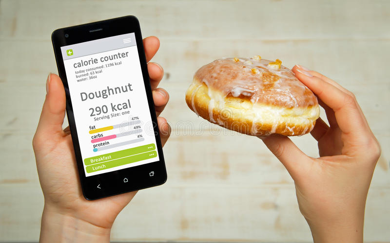 Calorie counter concept. Young woman holding mobile phone with calorie counter app on the screen stock photography