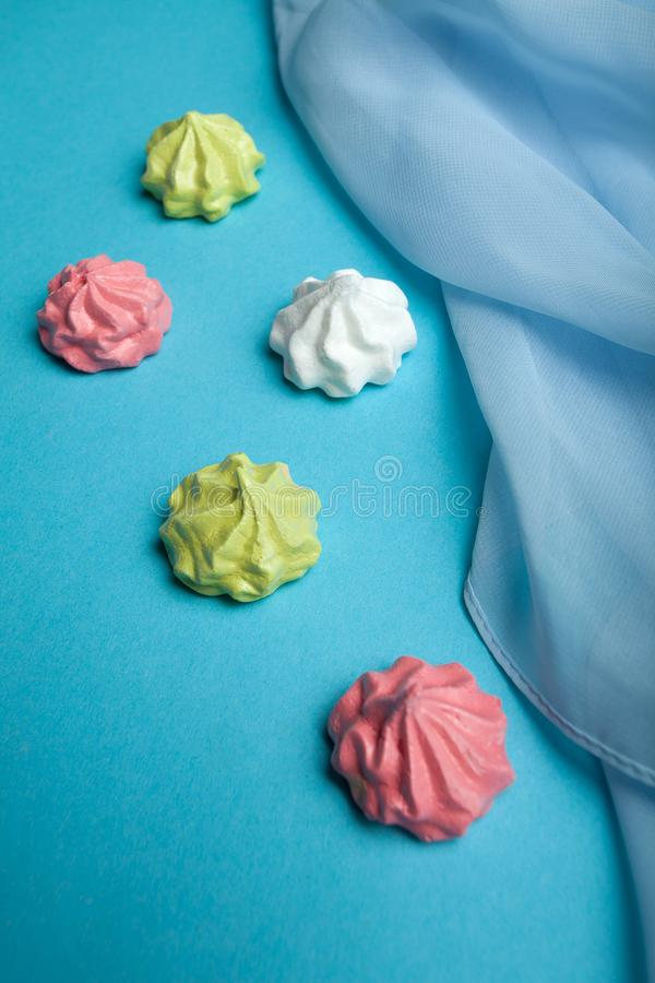 Calorie sweet French temptation meringue on a blue background royalty free stock photos