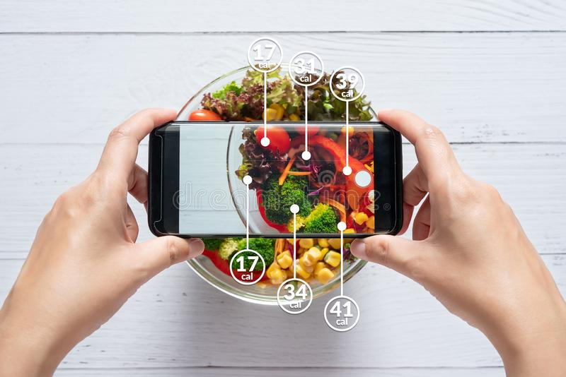 Calories counting and food control concept. woman using application on smartphone for scanning the amount of calories in the food. Before eat royalty free stock photo