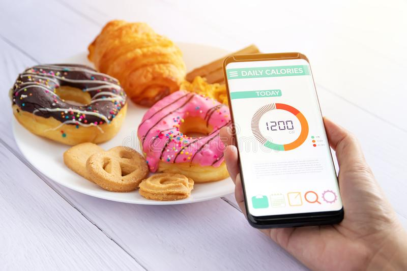 Calories counting and food control concept. woman using Calorie counter application on her smartphone with doughnut ,snack royalty free stock photo