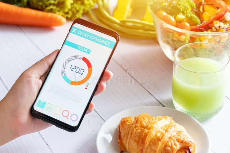 Calories counting and food control concept. woman using Calorie counter application on her smartphone with salad , vegetable stock images