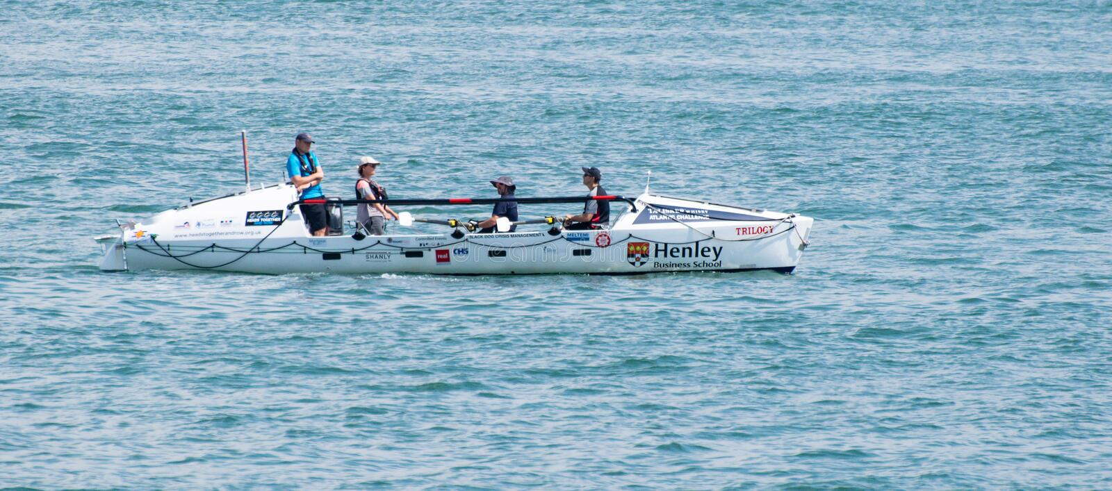 Trilogy Rowing boat. Calshot, United Kingdom - July 21 2018: A rowing boat called Trilogy sponsored by Henley Business school rows into the Solent stock image