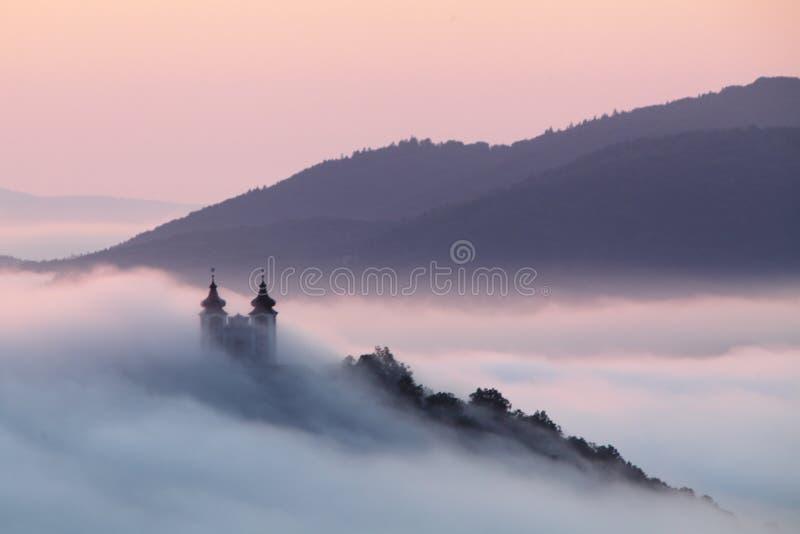 Calvary över moln i Banska Stiavnica, Slovakien arkivfoto