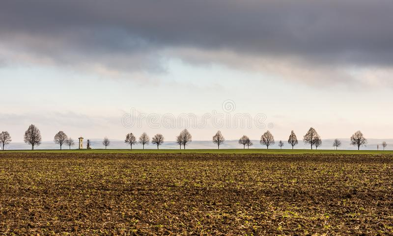Calvary with trees near the agriculture field. Meadow and countryside in czech republic. Thunder clouds above religion building. royalty free stock photos