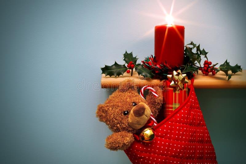 Calza di natale con i presente candela ed agrifoglio. immagine stock