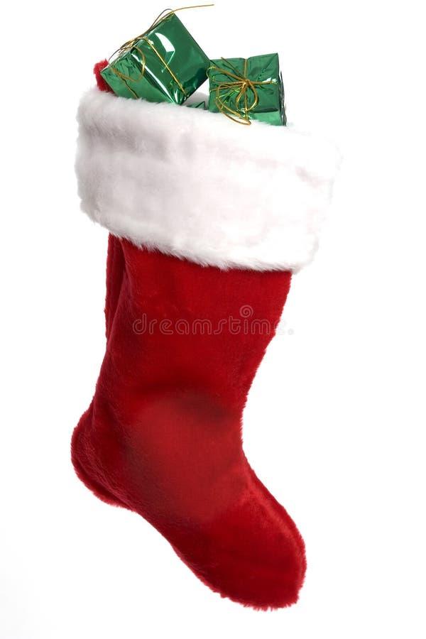 Calza rossa luminosa di natale con i presente fotografie stock