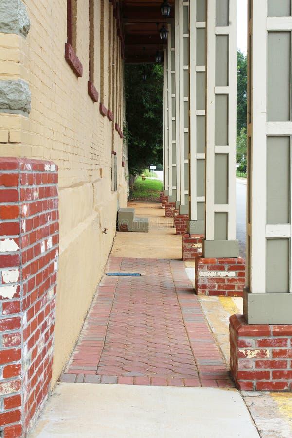 Calzada columned larga con las paredes de ladrillo y las pavimentadoras rojas fotos de archivo libres de regalías