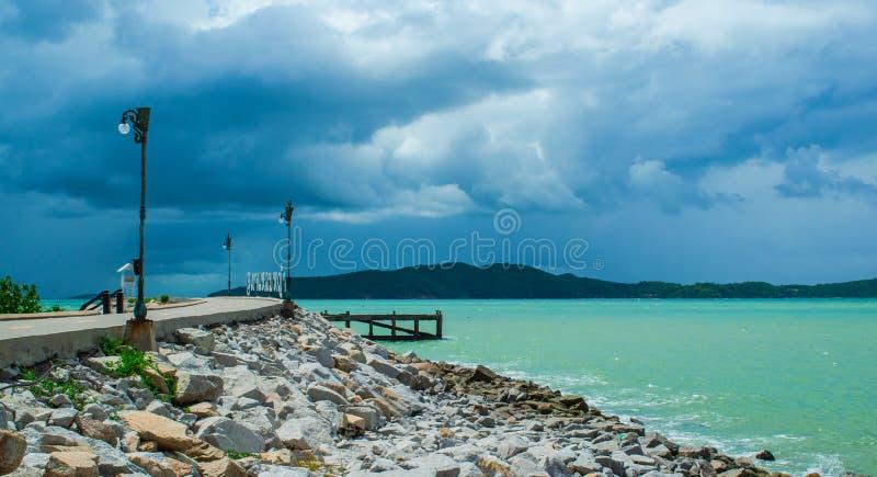 Calzada de la playa del mar y fondo oscuro hermoso de las nubes en Khao Lam Ya, Rayong, Tailandia fotos de archivo libres de regalías