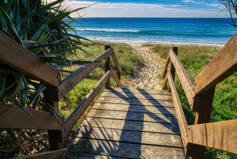 Calzada de madera que lleva a la playa arenosa, costa Australia de la sol de Queensland fotos de archivo libres de regalías
