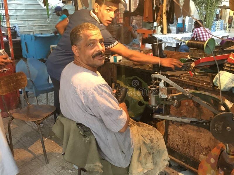 Calzado de inclinación sonriente diligente profesional del zapatero en la máquina en taller en ciudad turística foto de archivo libre de regalías