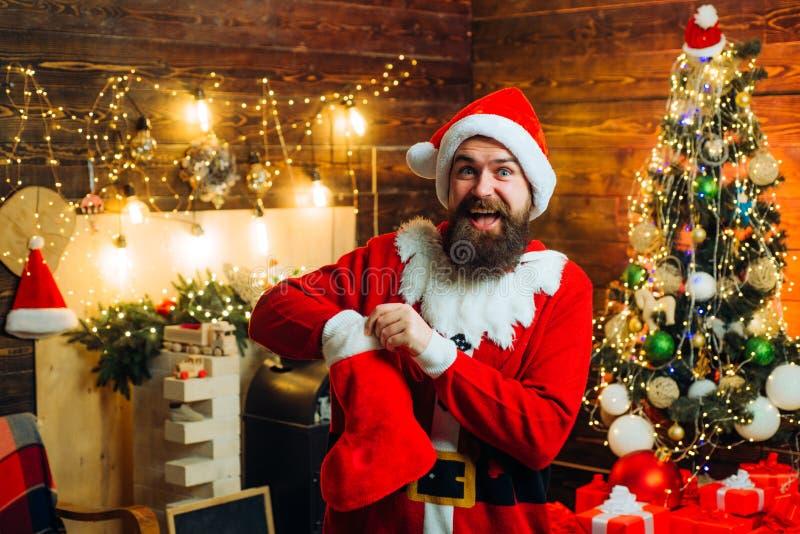 Calze di natale Designazione dei pantaloni a vita bassa di Santa con una barba lunga che posa sui precedenti di legno di Natale E fotografia stock libera da diritti
