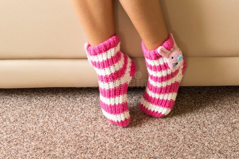 Calzini rosa divertenti sulle gambe di una bambina fotografie stock