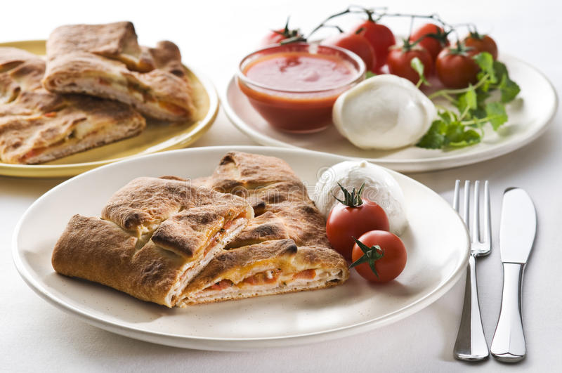 Calzone. Freshly baked calzone with mozzarella, tomato and basil royalty free stock photography
