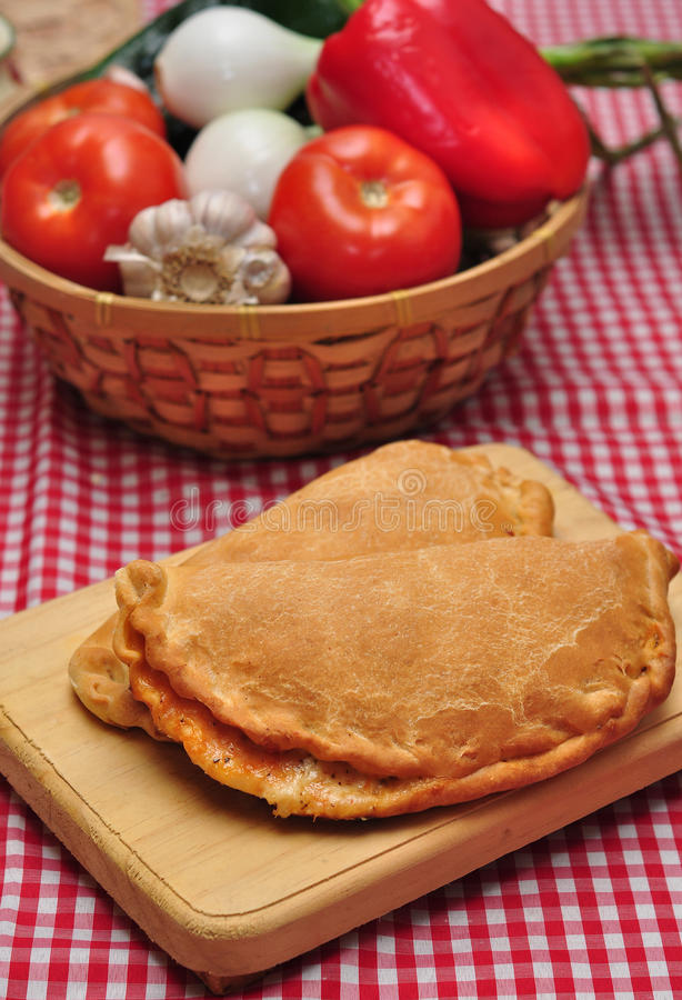 Calzone. On wooden plate, on a table with fresh ingredientes and checkered tablecloth stock photos