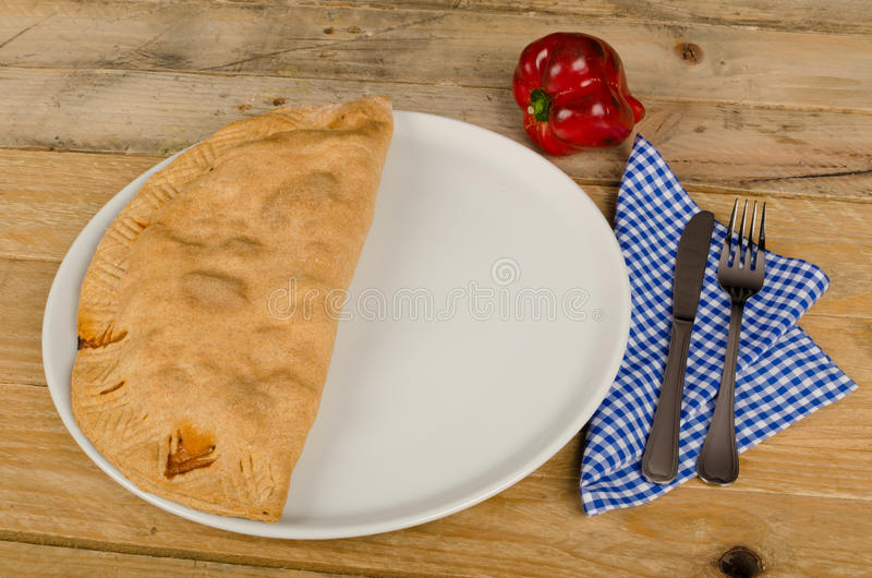 Calzone. Freshly baked homemade calzone on a rustic table stock photo