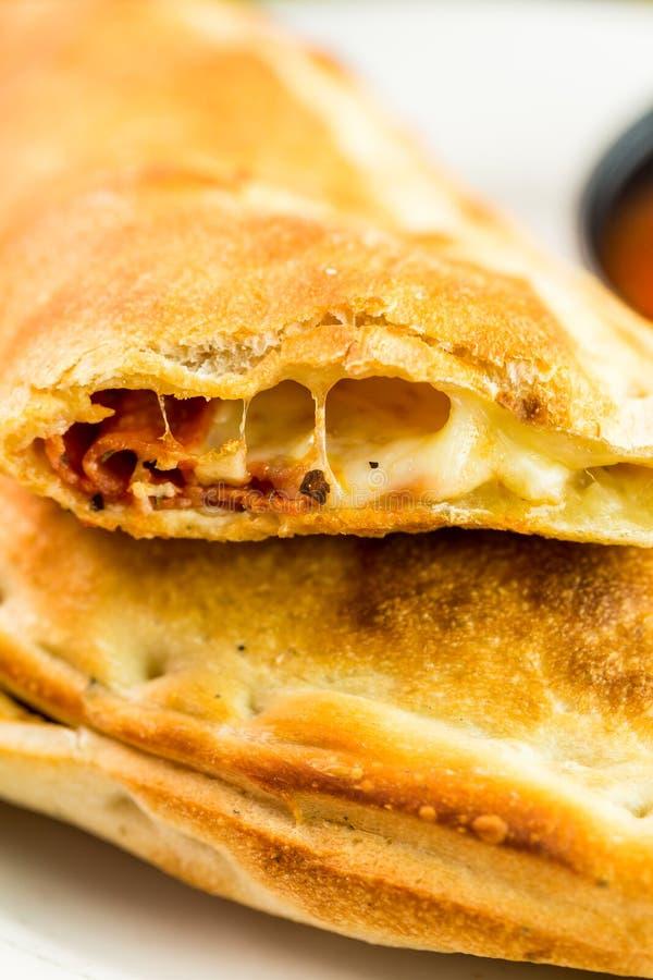 Calzone. Freshly made Pepperoni calzone in Italian restaurant stock photos