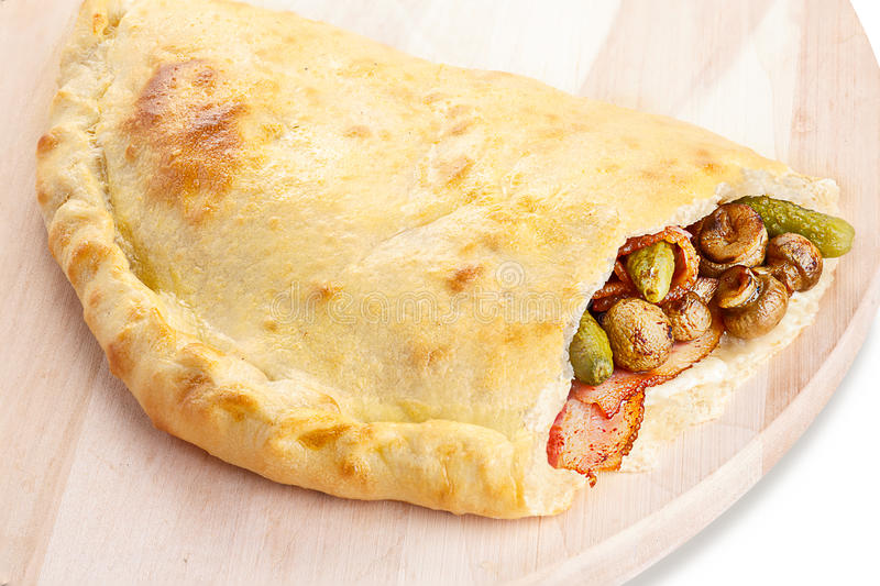 Calzone. Neat, tasty and elegant closed pizza (calzone) stuffed with bacon,mushrooms and gherkins royalty free stock image