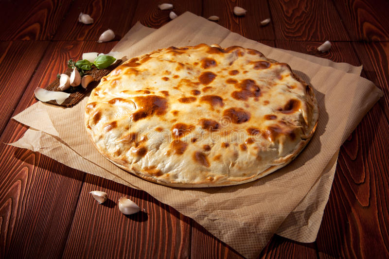 Calzone. Pizza Calzone with Chicken and Cheese on Parchment royalty free stock images