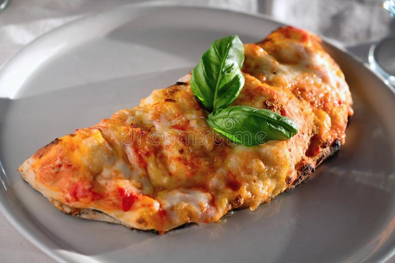 Calzone pizza. Chicken calzone pizza on lettuce leaves stock photos